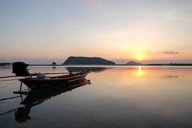 Barco no mar rodeado por colinas com o sol refletindo na água durante o pôr do sol