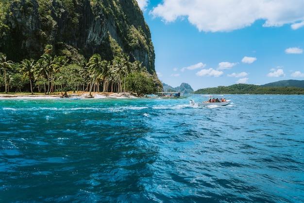 Barco perto da praia exótica no arquipélago bacuit, el nido, palawan, filipinas.