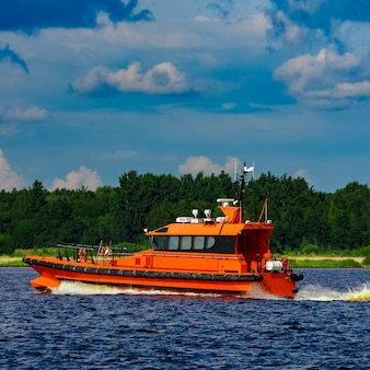 Barco-piloto laranja movendo-se à beira do rio na europa. serviço de resgate
