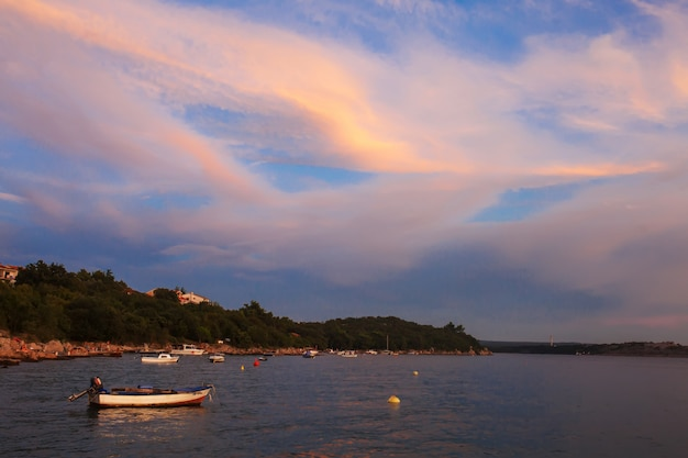 Barco solitário por do sol com céu dramático. pôr do sol em alto mar com um navio de pesca no horizonte.