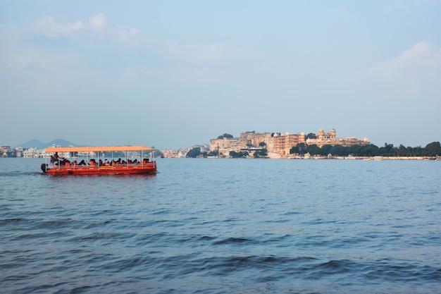 Barco toruist no lago pichola com o palácio da cidade em segundo plano. udaipur, índia