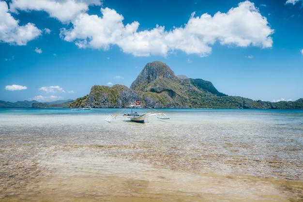 Barco tradicional atracado em lagoa azul rasa localizada em el nido, filipinas