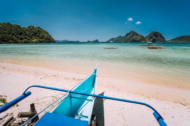 Barco tradicional banca na praia com lagoa azul e um cenário de natureza exótica de el nido, palawan, filipinas.