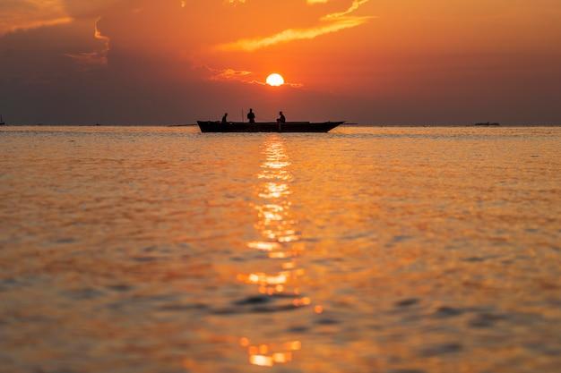Barco tradicional pescador dhow durante o pôr do sol no oceano índico na ilha de zanzibar, tanzânia, áfrica oriental