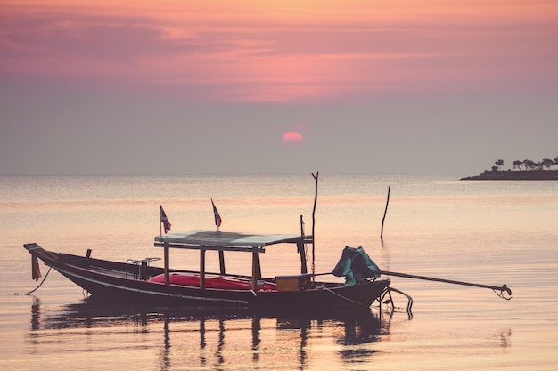 Barco tradicional tailandês ao pôr do sol