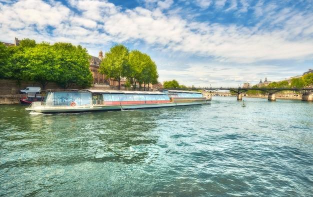 Barco turístico passa abaixo da pont des arts, no rio sena, em paris