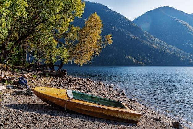 Barco velho de metal amarelo na margem de um lago de montanha. cair. rússia, república de altai, lago teletskoye
