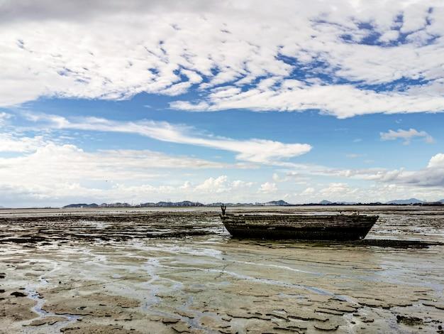 Barco velho e danificado na praia