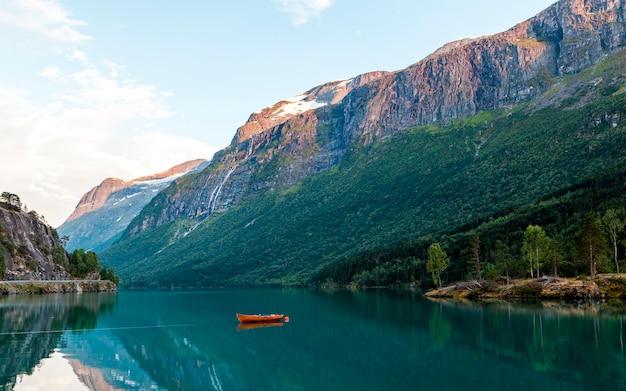 Barco vermelho atracado no lago idílico perto das montanhas rochosas