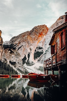 Barco vermelho em corpo d'água perto de casa de madeira marrom durante o dia