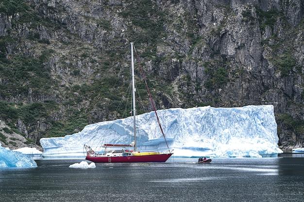 Barco vermelho na água ao lado de iceberg