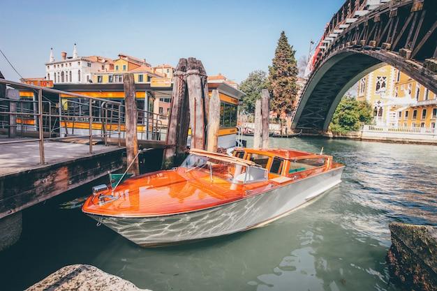 Barco via navegável laranja em um rio debaixo de uma ponte perto de edifícios em veneza, itália