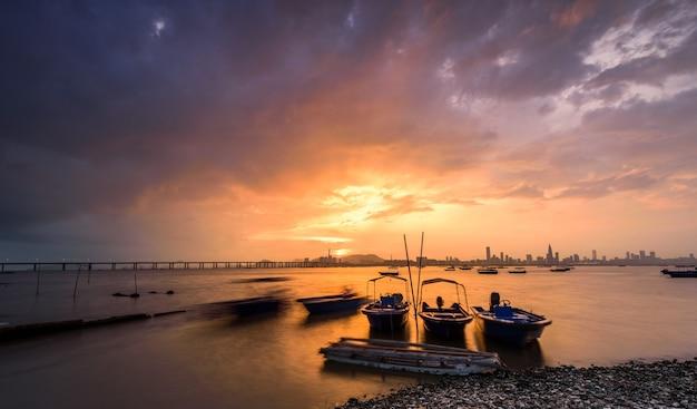 Barcos a motor estacionados na água junto à água com o pôr do sol e uma cidade visível