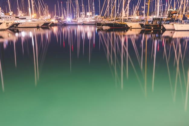 Barcos a vela e iates no porto à noite