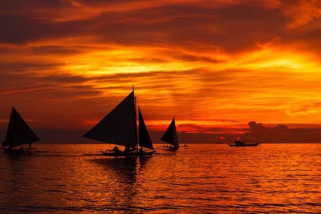 Barcos à vela no mar e pôr do sol dramático