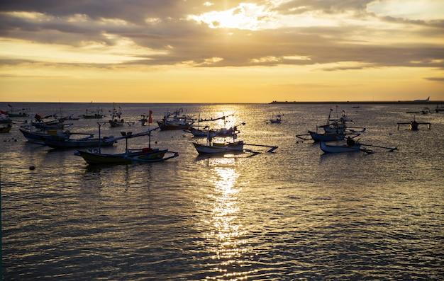 Barcos à vela no pôr do sol