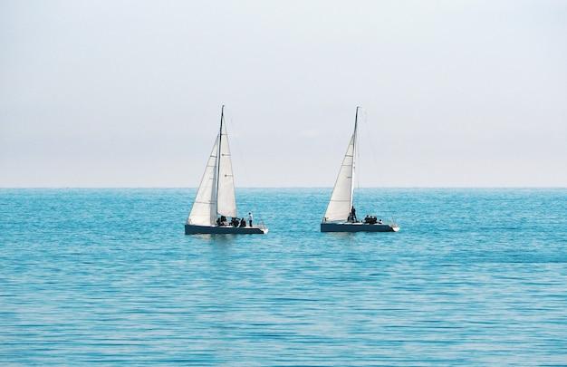 Barcos à vela para regata no fundo azul do mar e do céu