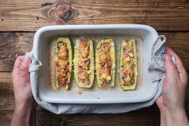Barcos assados recheados de abobrinha com cogumelos picados e legumes com queijo em uma assadeira. vista superior copyspace