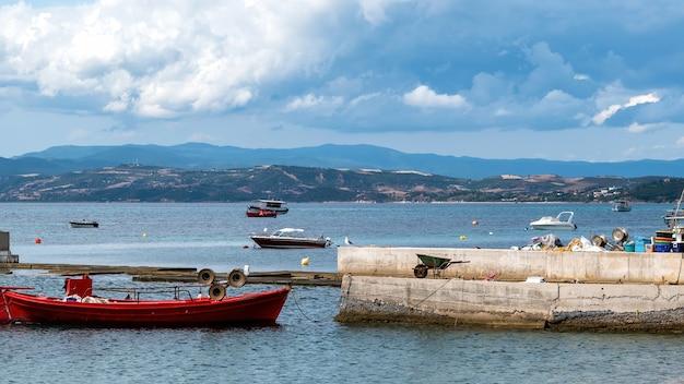 Barcos atracados e em movimento na costa do mar egeu, dois cais em primeiro plano, colina na parte de trás, ouranoupolis, grécia