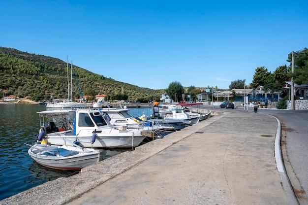 Barcos atracados na água perto da rua de aterro com edifícios e restaurantes, muito verde, colinas verdes, grécia