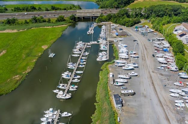 Barcos com vista aérea em um pequeno porto no oceano, uma pequena marina ao longo do cais
