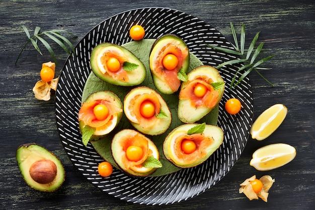 Barcos de abacate com salmão defumado, limão, physalis e folhas de hortelã, vista superior no escuro