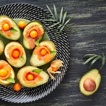 Barcos de abacate com salmão defumado, limão, physalis e folhas de hortelã, vista superior
