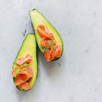 Barcos de abacate maduros com fatias de truta salgada, salmão e verduras frescas. barcos de abacate recheados com salmão com limão, folhas de espinafre e rúcula, comida saudável de conceito, dieta.