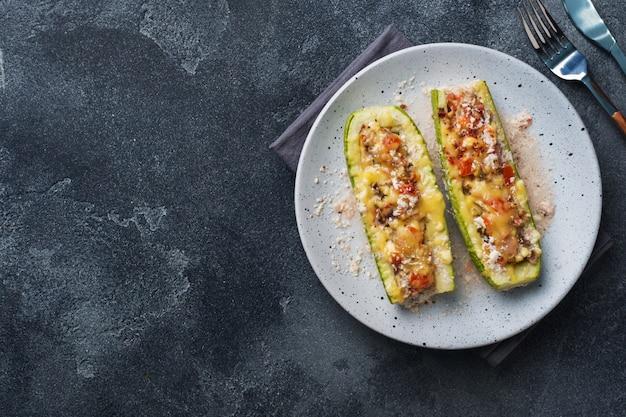 Barcos de abobrinha recheada assada com cogumelos picados de frango e legumes com queijo em um prato. copyspace