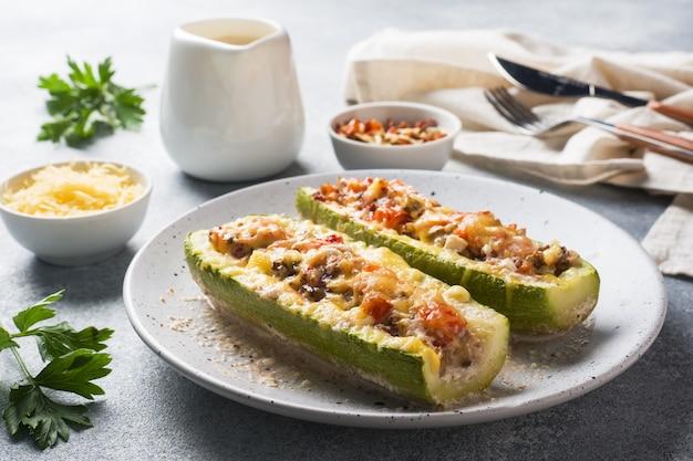 Barcos de abobrinha recheada assada com cogumelos picados de frango e legumes com queijo em um prato.