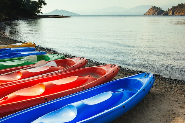 Barcos de canoa coloridos na praia, mar e montanhas no