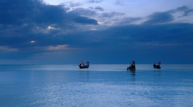 Barcos de cauda longa no mar e céu azul ao entardecer na ilha de samui, tailândia