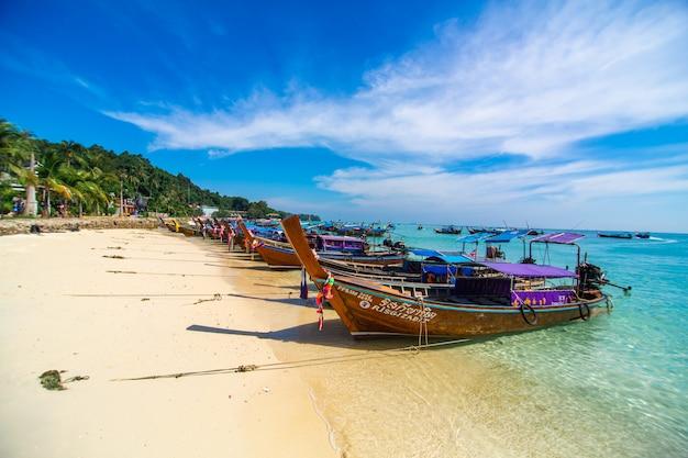 Barcos de madeira da pesca tailandesa tradicional envolvidos com fitas coloridas. na costa de areia da ilha tropical.