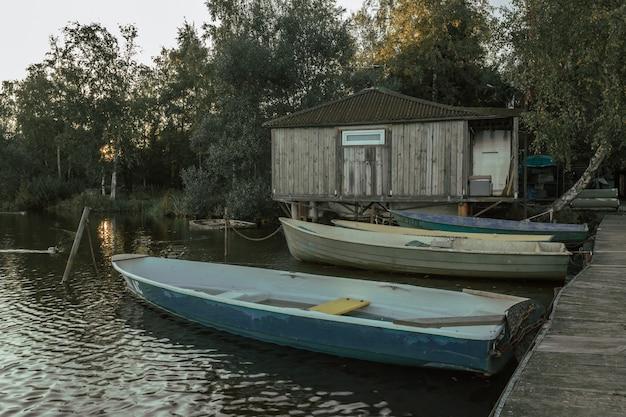 Barcos de madeira no cais com a casa do pescador à noite.