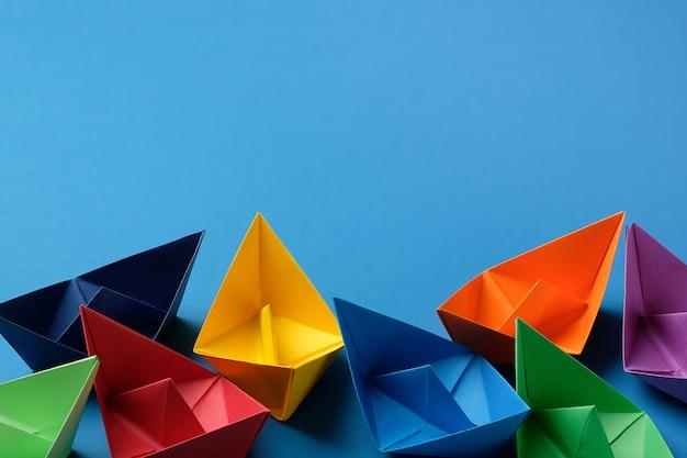 Barcos de papel coloridos em uma superfície azul brilhante. copie o espaço