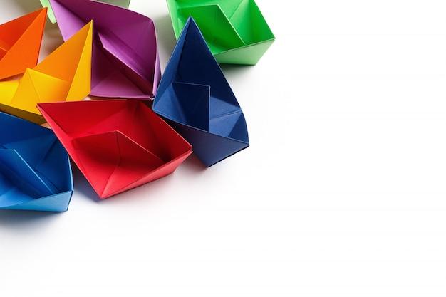 Barcos de papel coloridos em uma superfície branca brilhante. copie o espaço