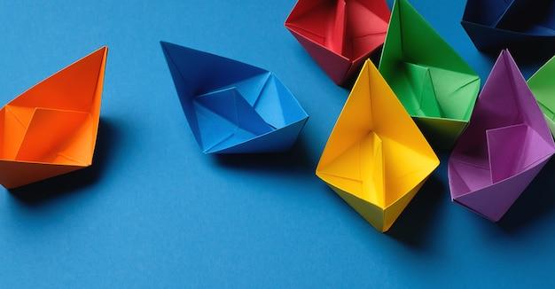 Barcos de papel coloridos sobre um fundo azul brilhante. copie o espaço