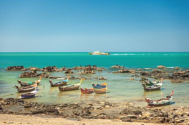 Barcos de pesca de madeira coloridos de estilo tailandês estão junto à costa rochosa, tendo como pano de fundo o mar com um barco de passageiros e céu azul.
