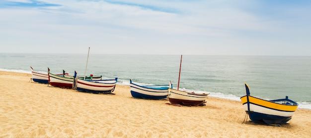 Barcos de pesca de madeira multicoloridos bonitos em uma praia arenosa