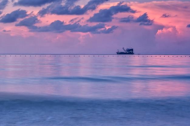 Barcos de pesca de madeira na praia do mar ao nascer do sol da manhã