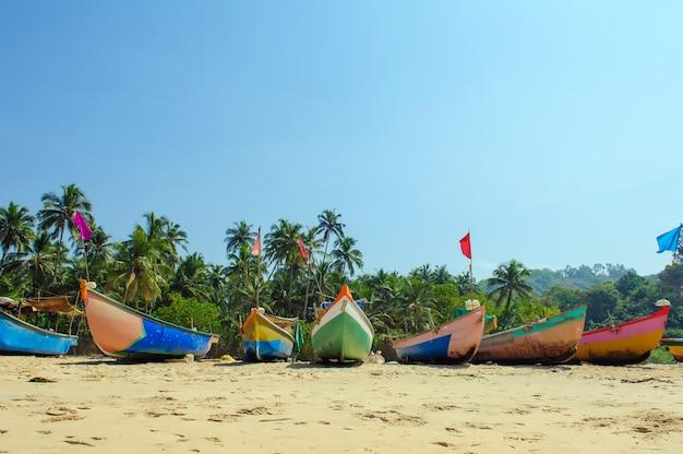 Barcos de pesca em cores de reggae na praia do oceano contra o céu azul