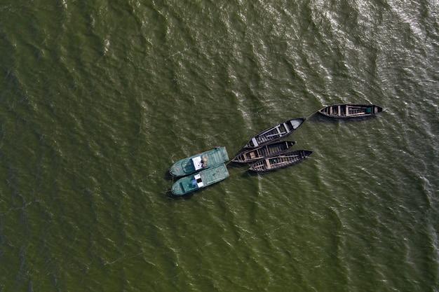 Barcos de pesca, flutuando nas águas calmas e indo para a pesca