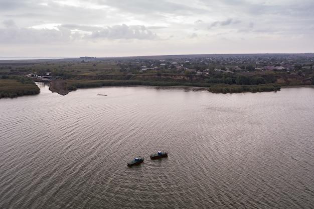 Barcos de pesca, flutuando nas águas calmas e indo pescar sob um céu de nuvens