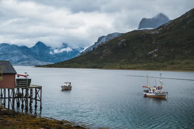 Barcos de pesca navegando no lago perto das montanhas sob o céu nublado