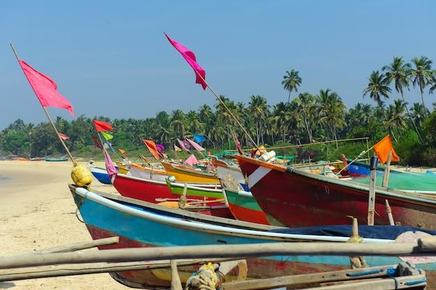 Barcos de pesca pequenos em cores da reggae no litoral da praia do oceano contra o céu azul. índia, goa, maharashtra.