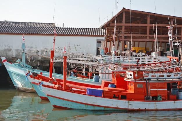 Barcos de pesca tailandeses tradicionais brilhantes para a pesca da noite dos camarões no porto.
