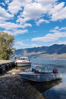 Barcos de recreio no cais de um lago de montanha rússia altai lago teletskoye cabo kyrsay