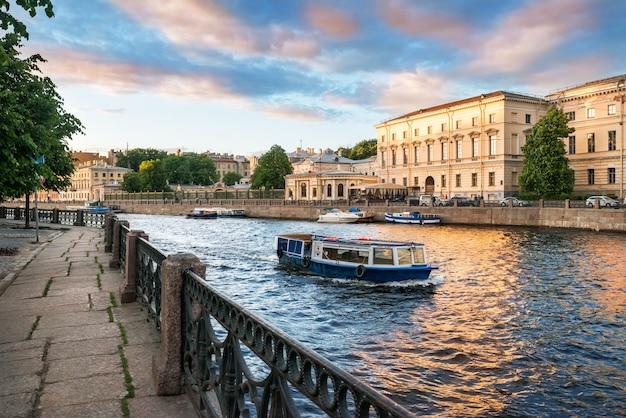 Barcos de recreio no rio fontanka em são petersburgo em uma noite ensolarada e o dique