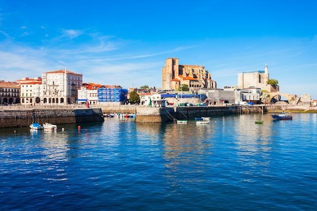 Barcos no porto de castro urdiales, igreja de santa maria e farol do castelo de santa ana na região da cantábria, no norte da espanha.
