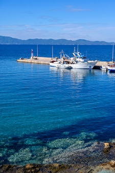 Barcos no porto de nea roda na água do mar azul, halkidiki, grécia